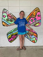 Fifth grader Ella Tobe shows off the student created wings inspired by muralist Kelsey Montague.