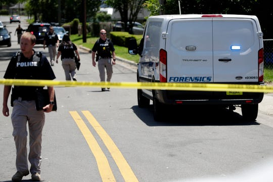 A forensics team and police officers work a crime scene in the surrounding areas of the intersection of Gibbs Drive and Alice Jackson Lane near Oakland Cemetery Tuesday, May 14, 2019. A victim was shot and killed.