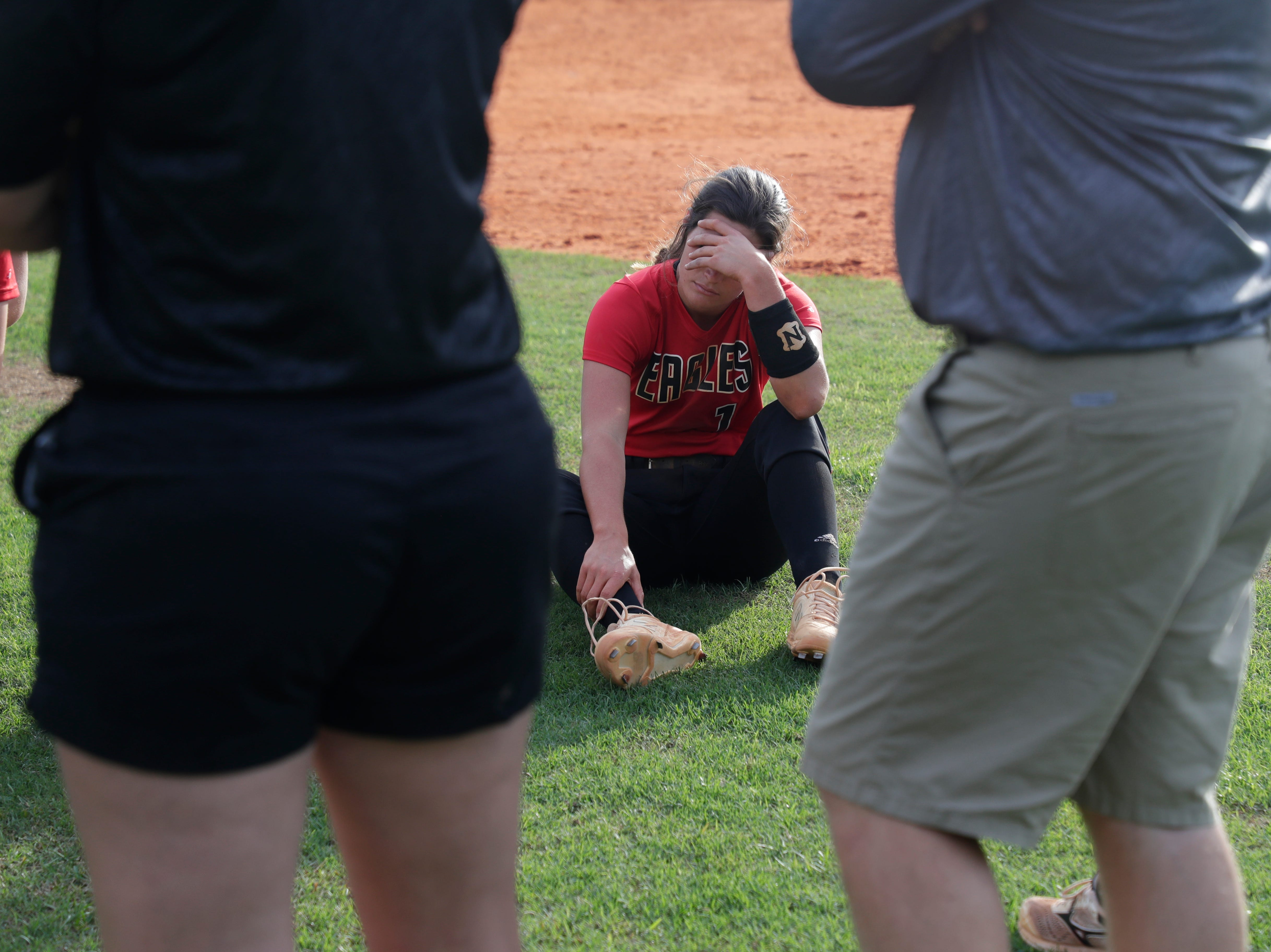 North Florida Christian's Chloe Culp covers her face as the team huddles after losing the 1-3A regional final game 16 to 11 to University Christian at NFC Tuesday, May 14, 2019.