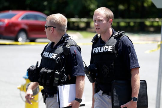 Two police officers leave the scene of a shooting near the intersection of Gibbs Drive and Alice Jackson Lane near Oakland Cemetery Tuesday, May 14, 2019. The shooting led to the death of the victim.