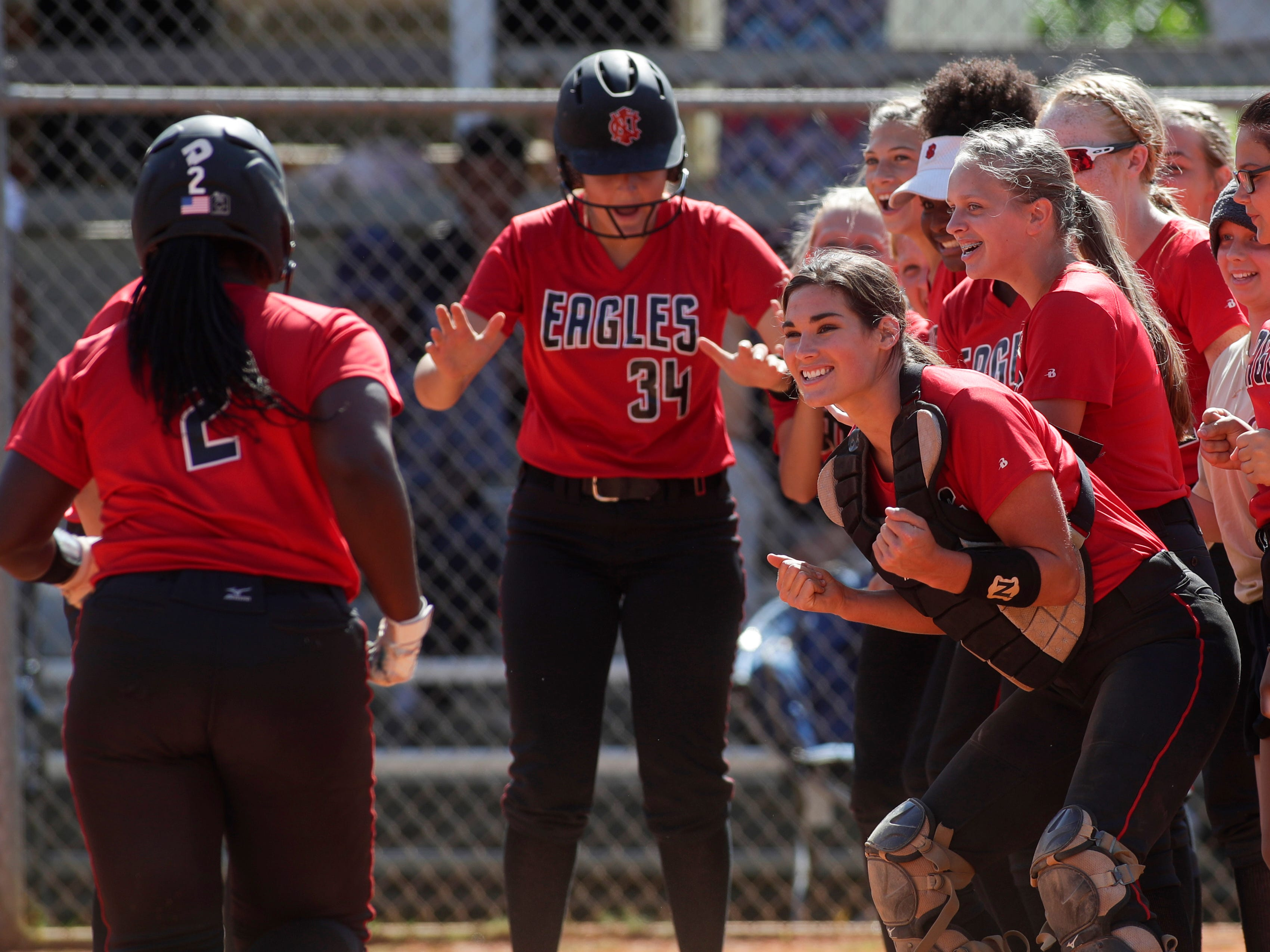 Chloe Culp (catching gear) and NFC's softball team congratulate Eva Holmes (2) on hitting a home run during the 1-3A regional final game between NFC and University Christian at NFC Tuesday, May 14, 2019. UC defeated NFC 16-11.