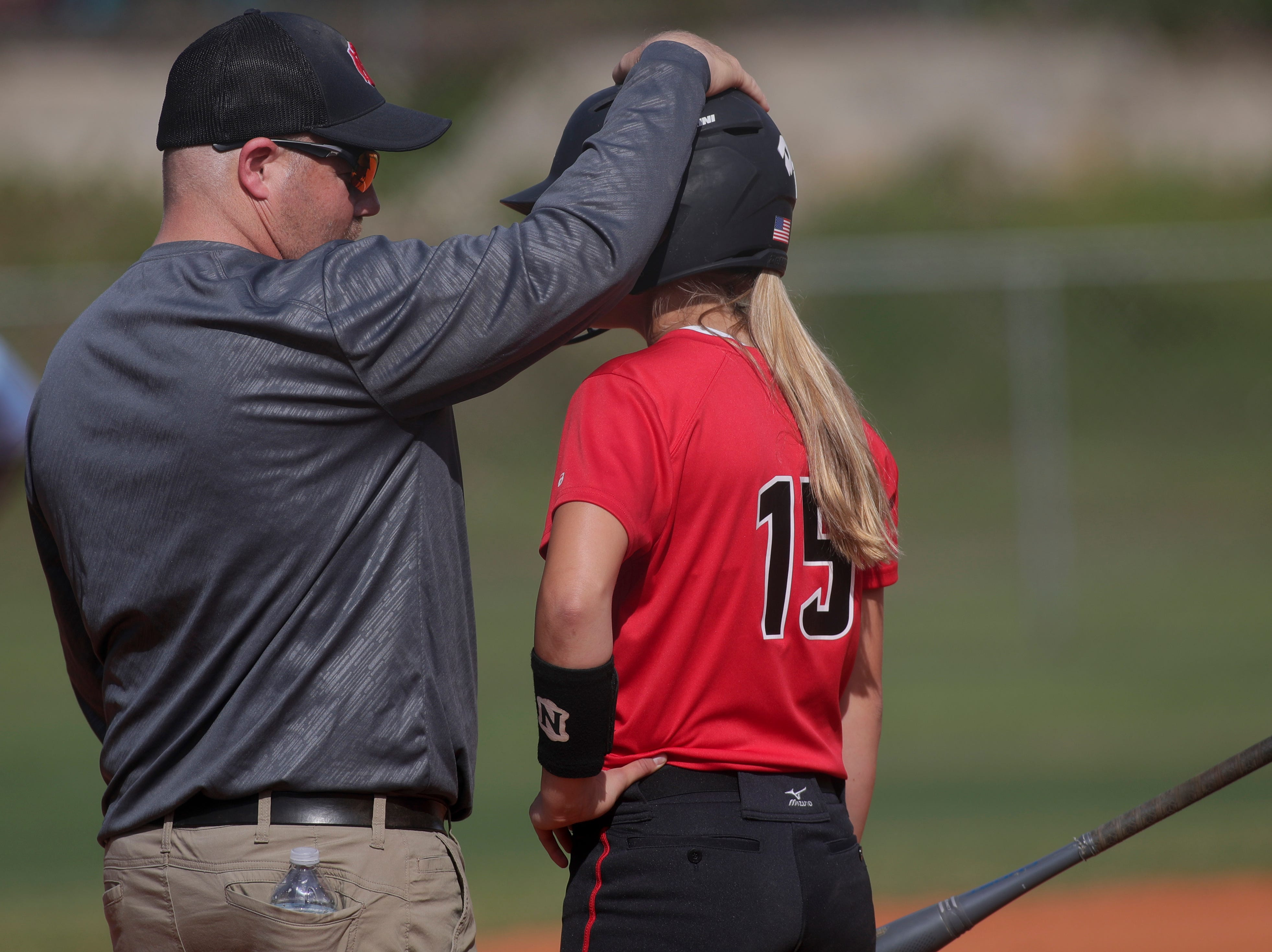 NFC softball coach Dennis Gorham gives Emma Brice (15) a pep talk before hitting during the 1-3A regional final game between NFC and University Christian at NFC Tuesday, May 14, 2019. UC defeated NFC 16-11 to advance to the state tournament.