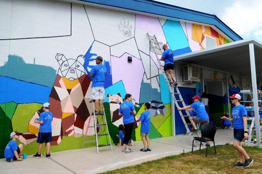 Volunteers work on the mural at Gilchrist designed by Sam Rosenstein with input from students.