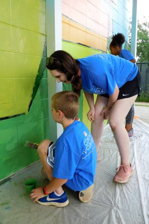 Gilchrist art teacher Victoria Mendenhall guides a student in painting.