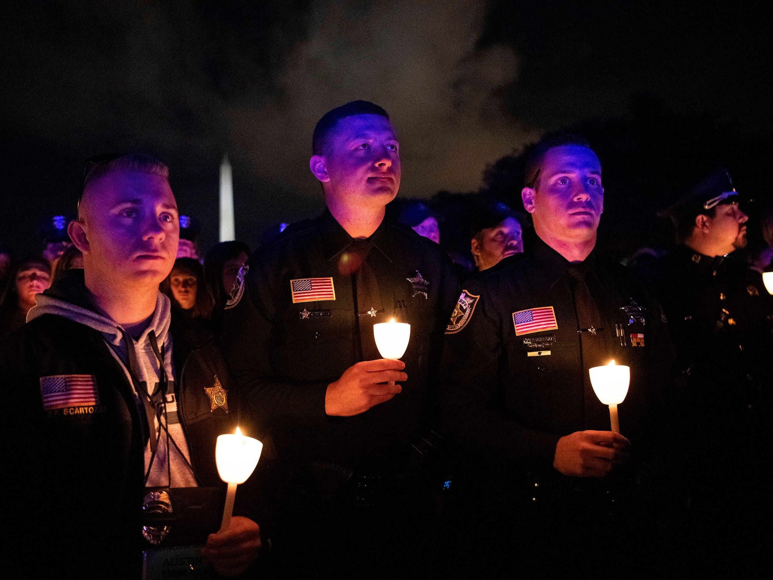 Austin Henley (from left), Joshua Gonzalez and Patrick Scartozzi, all police officers in West Palm Beach, hold candles on the National Mall in Washington, D.C., Monday, May 13, 2019, during a candlelight vigil to honor slain law enforcement officers as part of Police Week in the nation's capital.