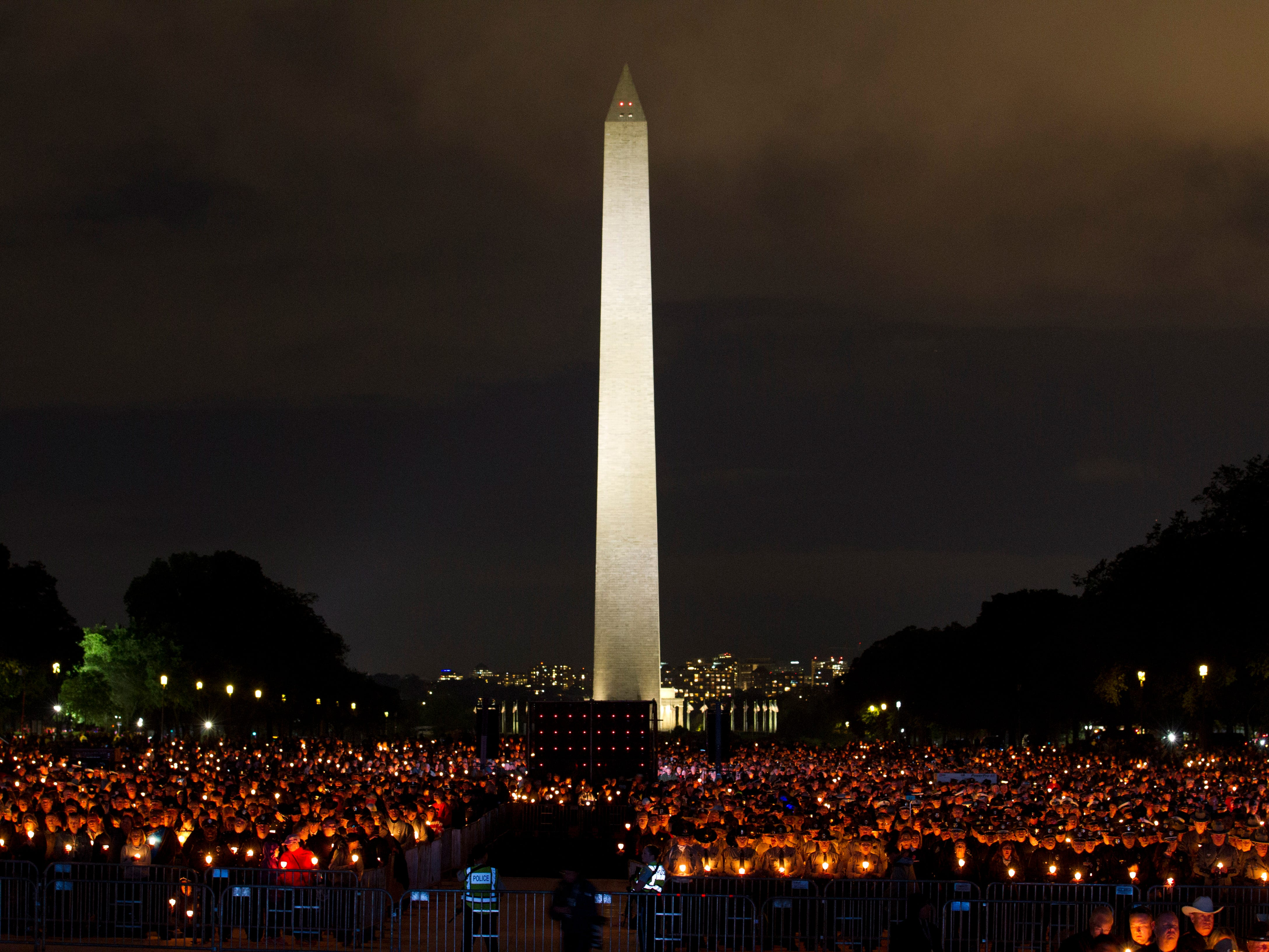 People hold candles, as the Washington Monument stands in the background, during the National Law Enforcement Officers Memorial Fund Annual Candlelight Vigil to commemorate new names added to the monument, in a ceremony at the National Mall in Washington, Monday, May 13, 2019.