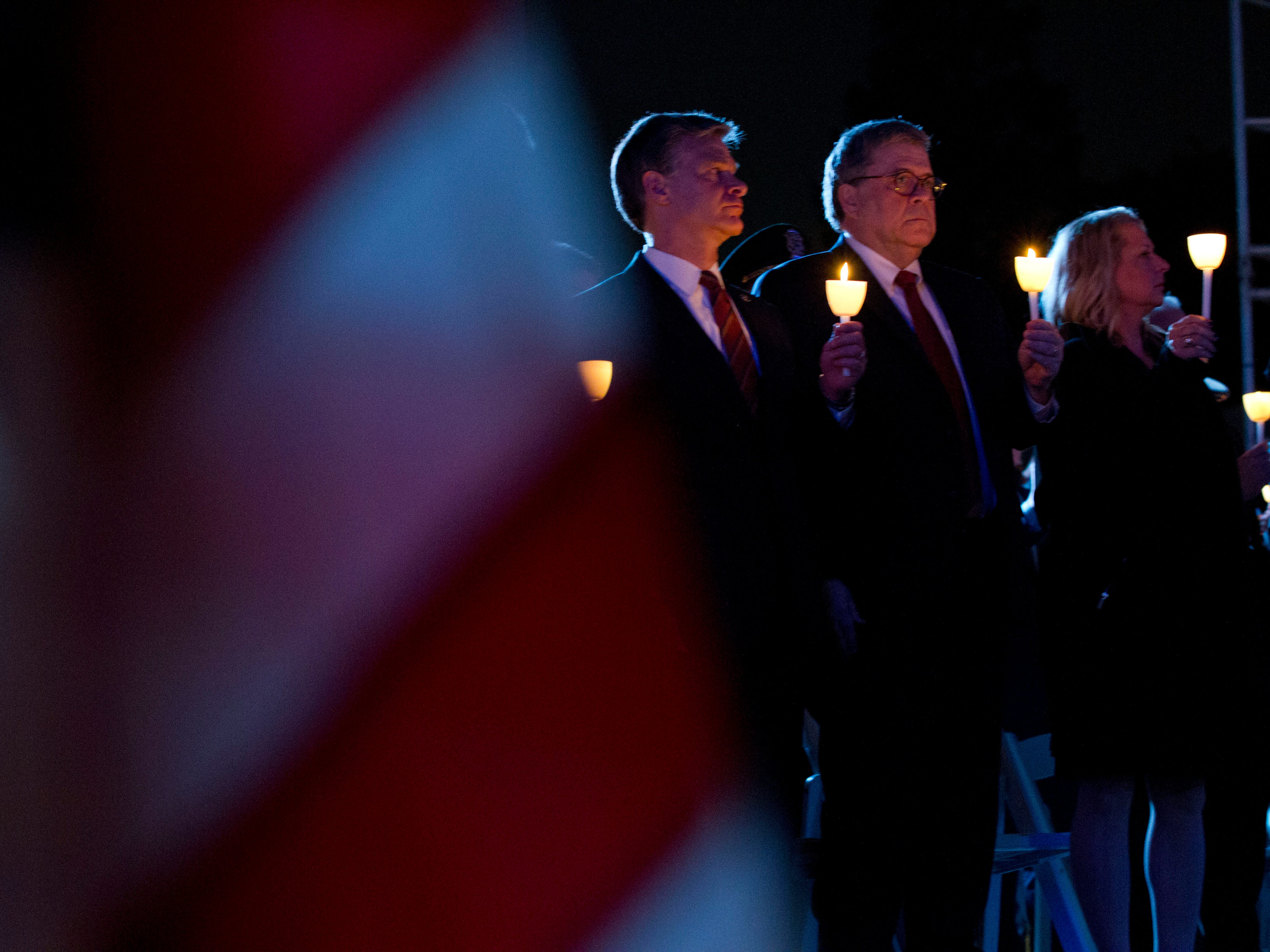 Attorney General William Barr, second from right, and FBI Director Christopher Wray, third from right, hold candles during the National Law Enforcement Officers Memorial Fund Annual Candlelight Vigil to commemorate new names added to the monument, in a ceremony at the National Mall in Washington, Monday, May 13, 2019.