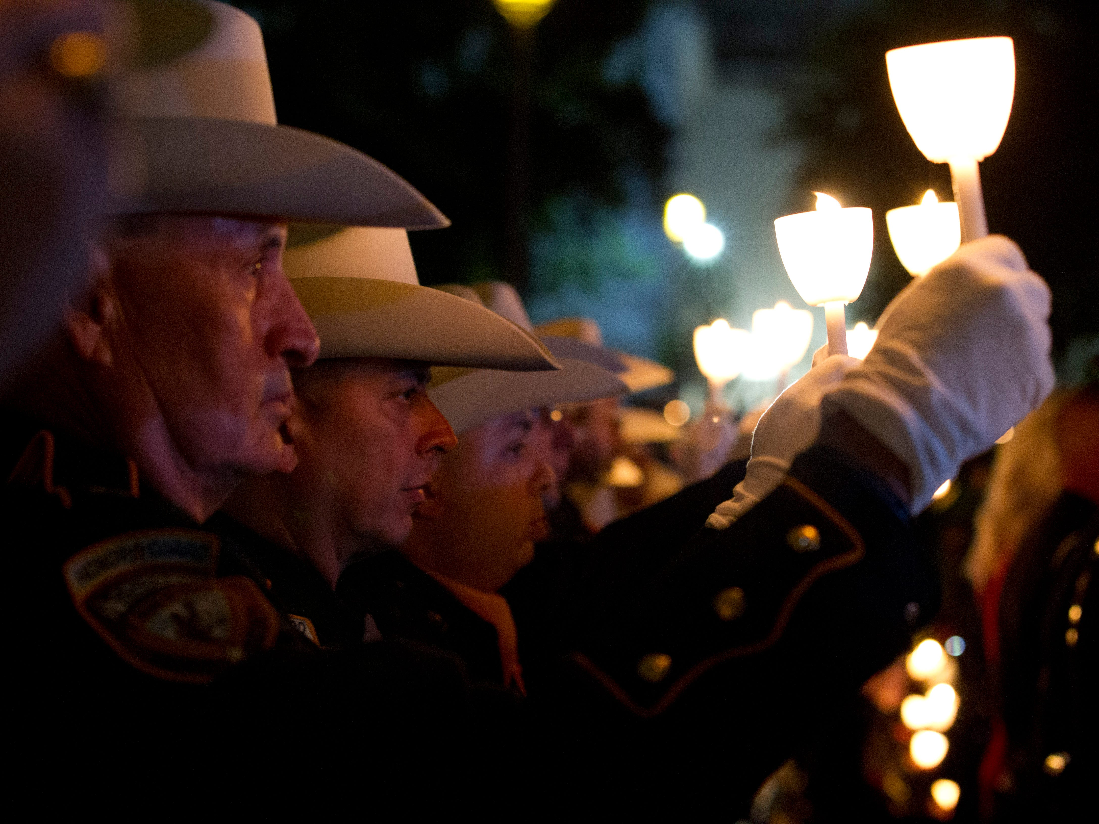 Houston law enforcement personnel raise their candles during the National Law Enforcement Officers Memorial Fund Annual Candlelight Vigil to commemorate new names added to the monument, in a ceremony at the National Mall in Washington, Monday, May 13, 2019.