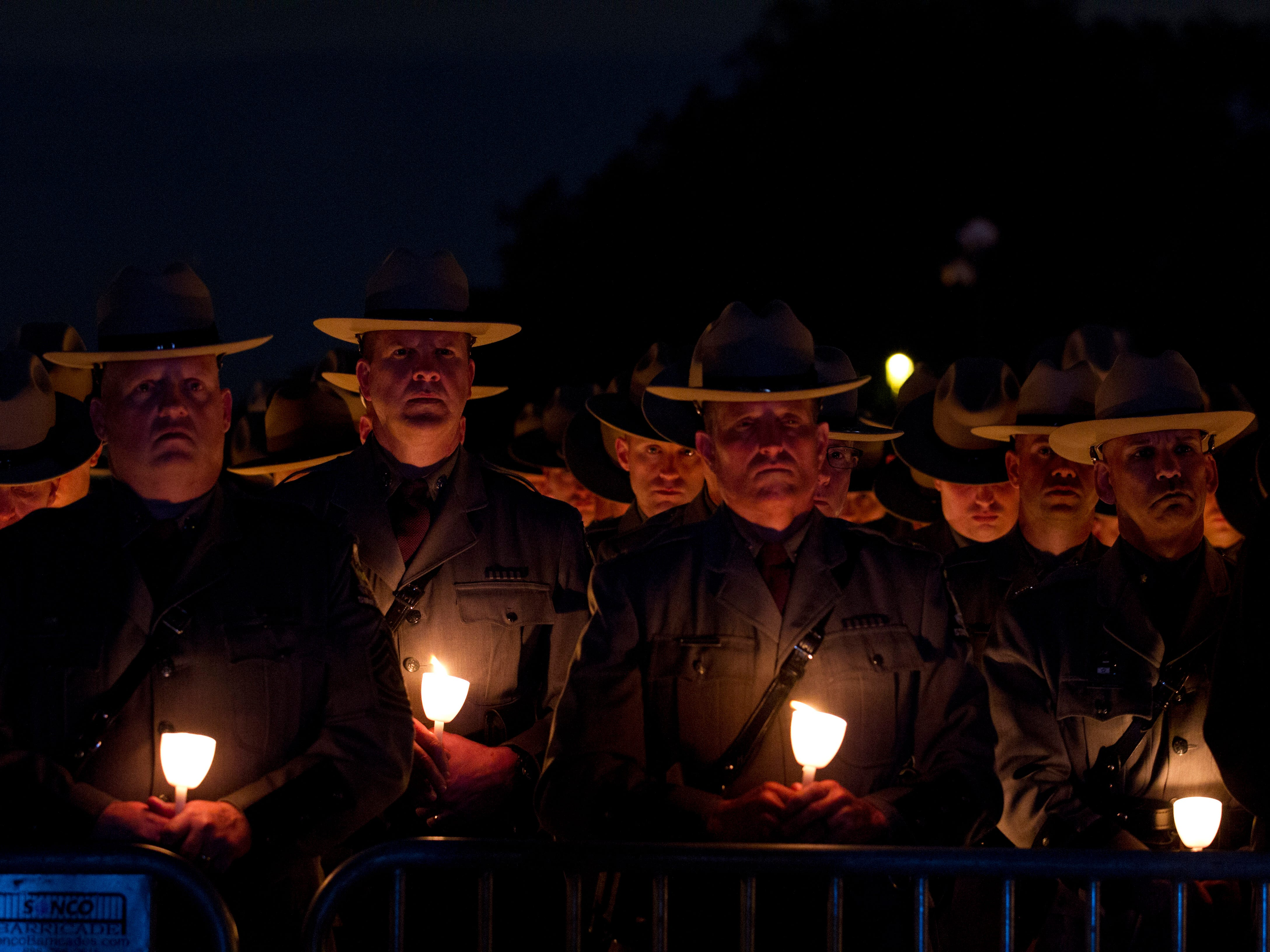Law enforcement personnel hold candles during the National Law Enforcement Officers Memorial Fund Annual Candlelight Vigil to commemorate new names added to the monument, in a ceremony at the National Mall in Washington, Monday May 13, 2019.
