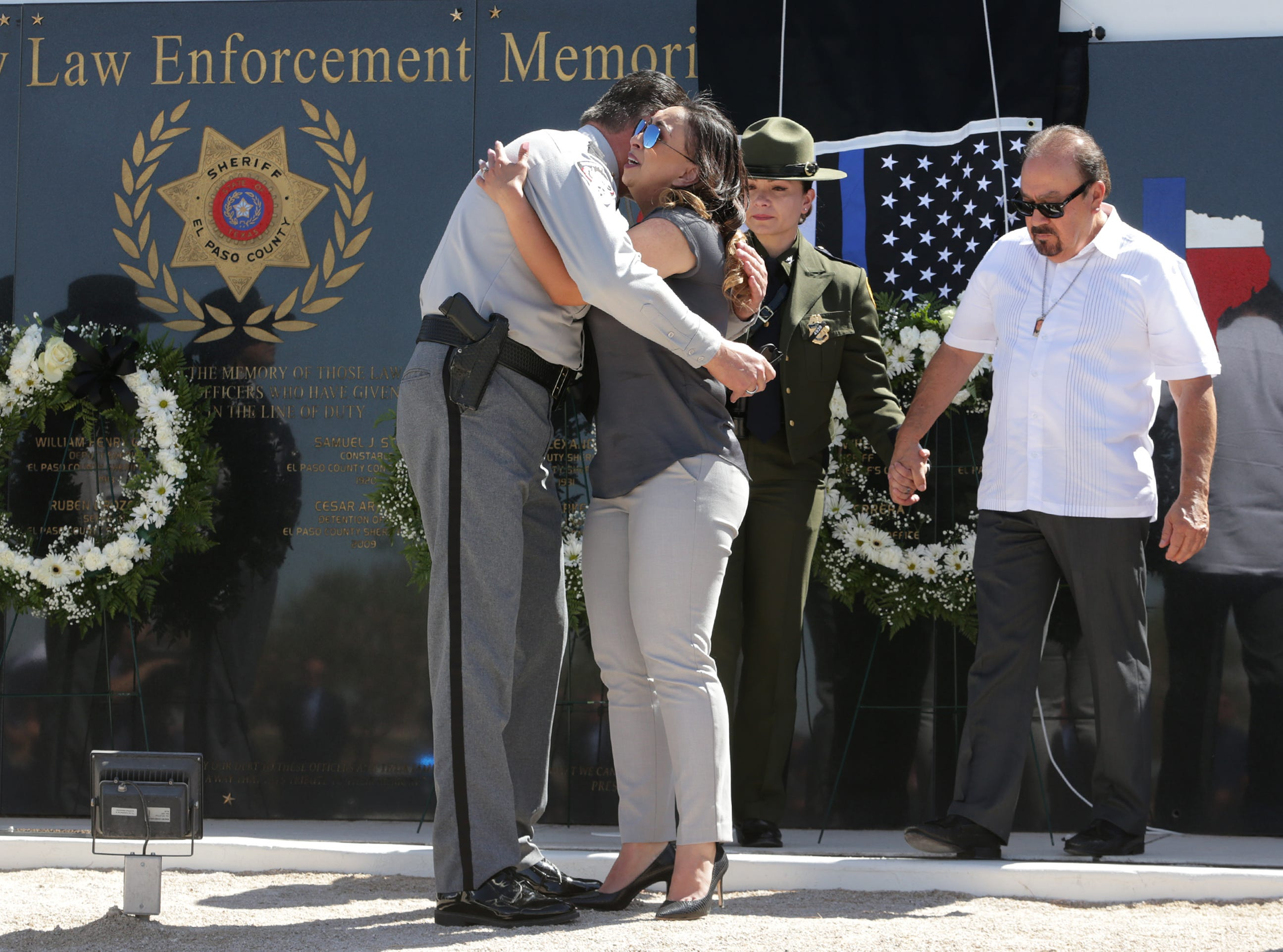 El Paso Sheriff Richard Wiles hugs Ashley Herrera, widow of Deputy Peter Herrera, who was killed in the line of duty, Tuesday, May 14, 2019, at the County Law Enforcement Memorial at the Sheriff's Office's headquarters in East El Paso. Fifteen law enforcement officers are honored on the memorial.