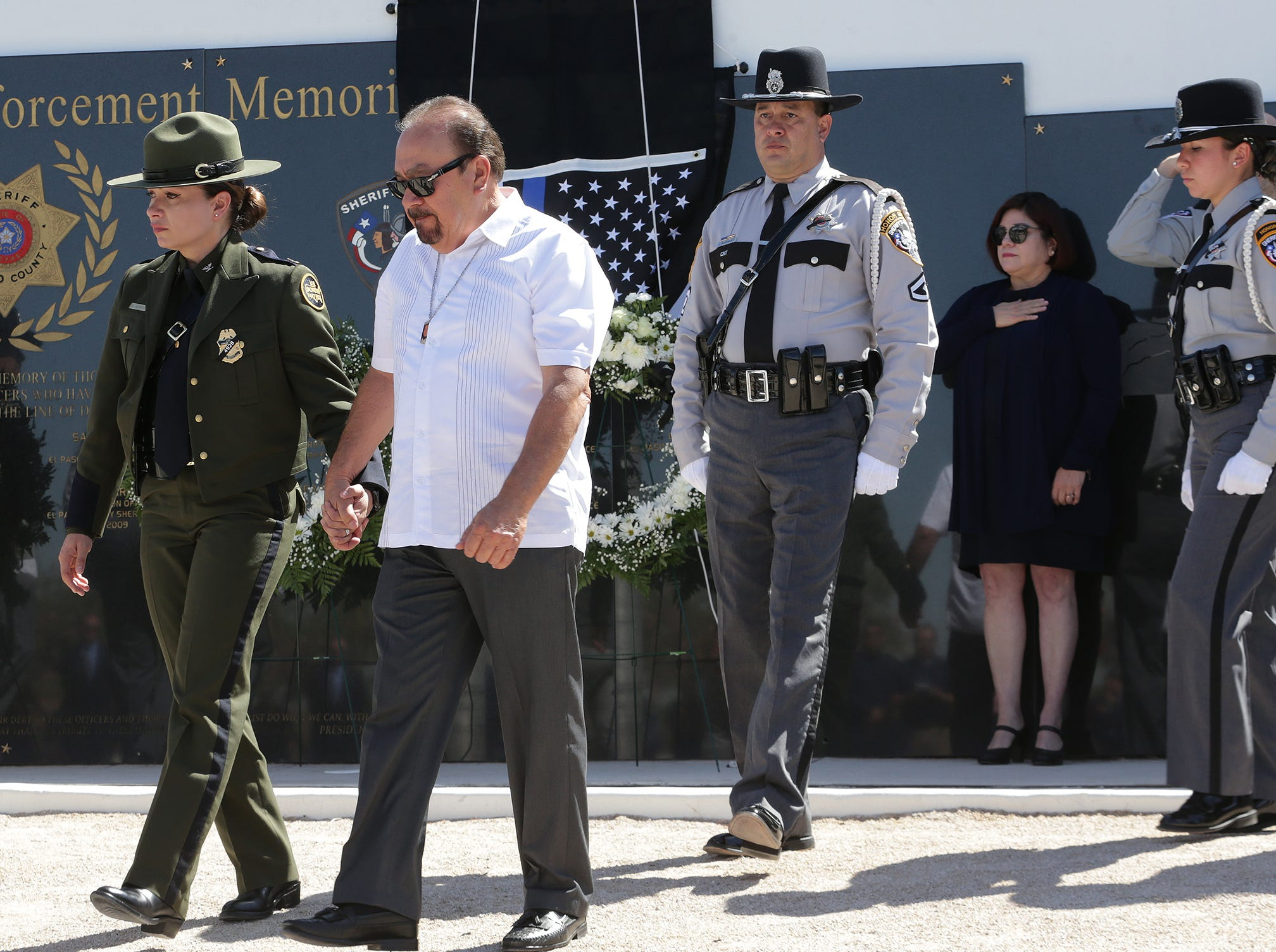 Luis Herrera is led from the memorial at the El Paso Sheriff's Office Tuesday after revealing his son Dep. Peter Herrera's name on the memorial.