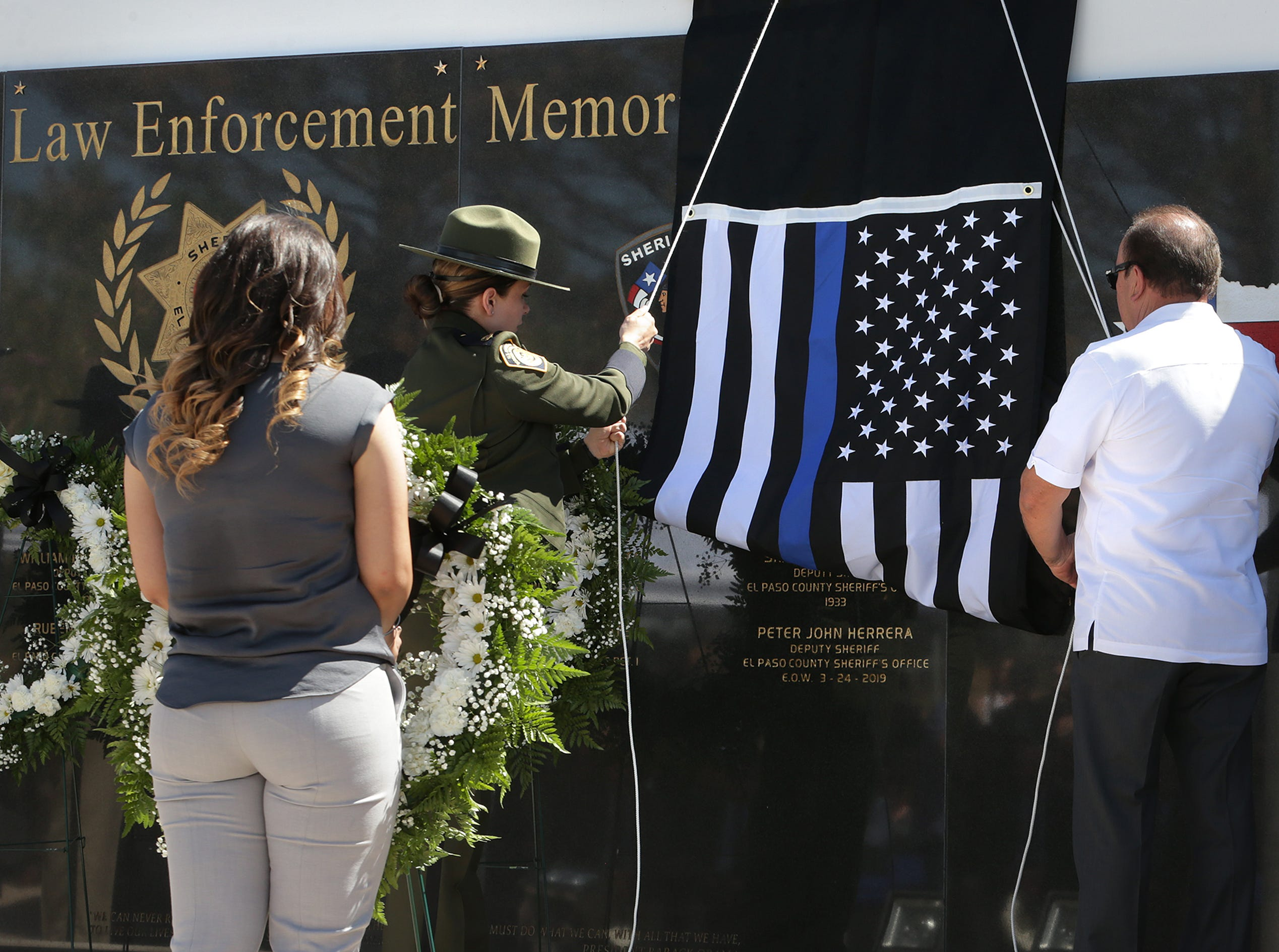 Luis Herrera unveils the name of his son, Deputy Peter Herrera, on the County Law Enforcement Memorial at the Sheriff's Office's headquarters in East El Paso on Tuesday, May 14, 2019, as Herrera's widow, Ashley Herrera, waits to place a wreath.