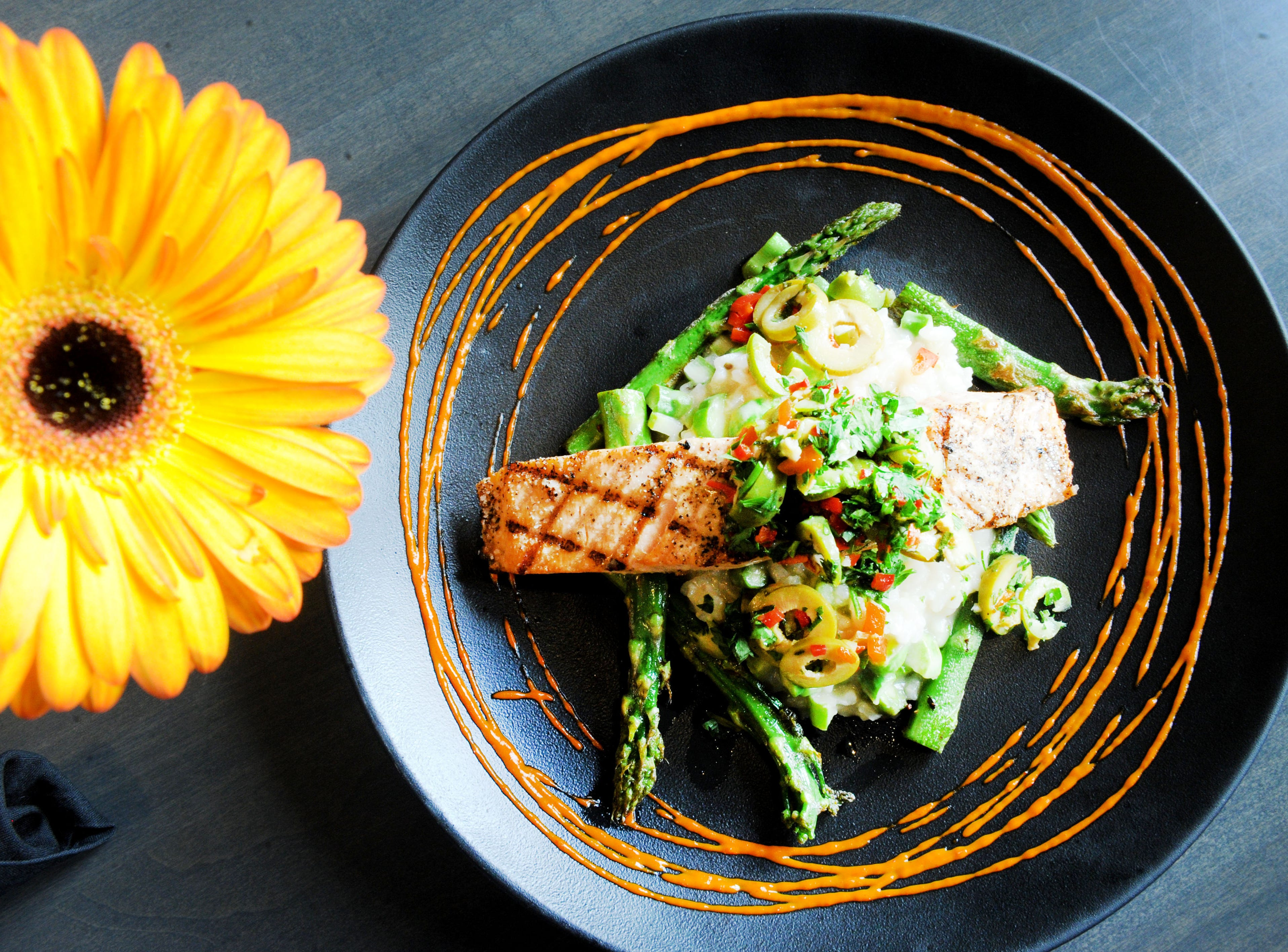 The grilled salmon is served with asparagus risotto, olive relish and roasted pepper aioli at Slate Bistro & Craft Bar in Camarillo.