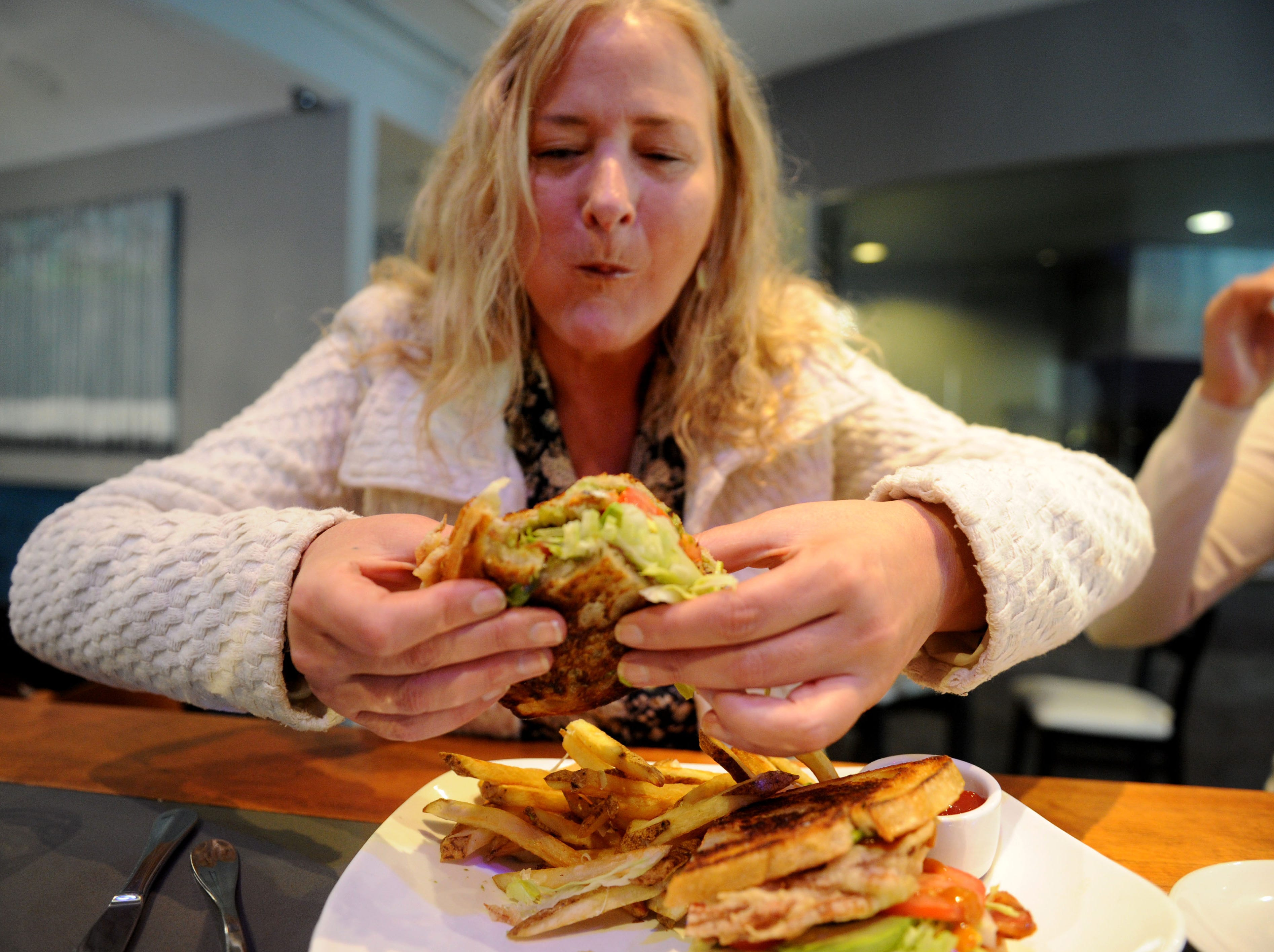 Robin Reed enjoys her fresh soft shell crab sandwich with French fries at Slate Bistro & Craft Bar in Camarillo.