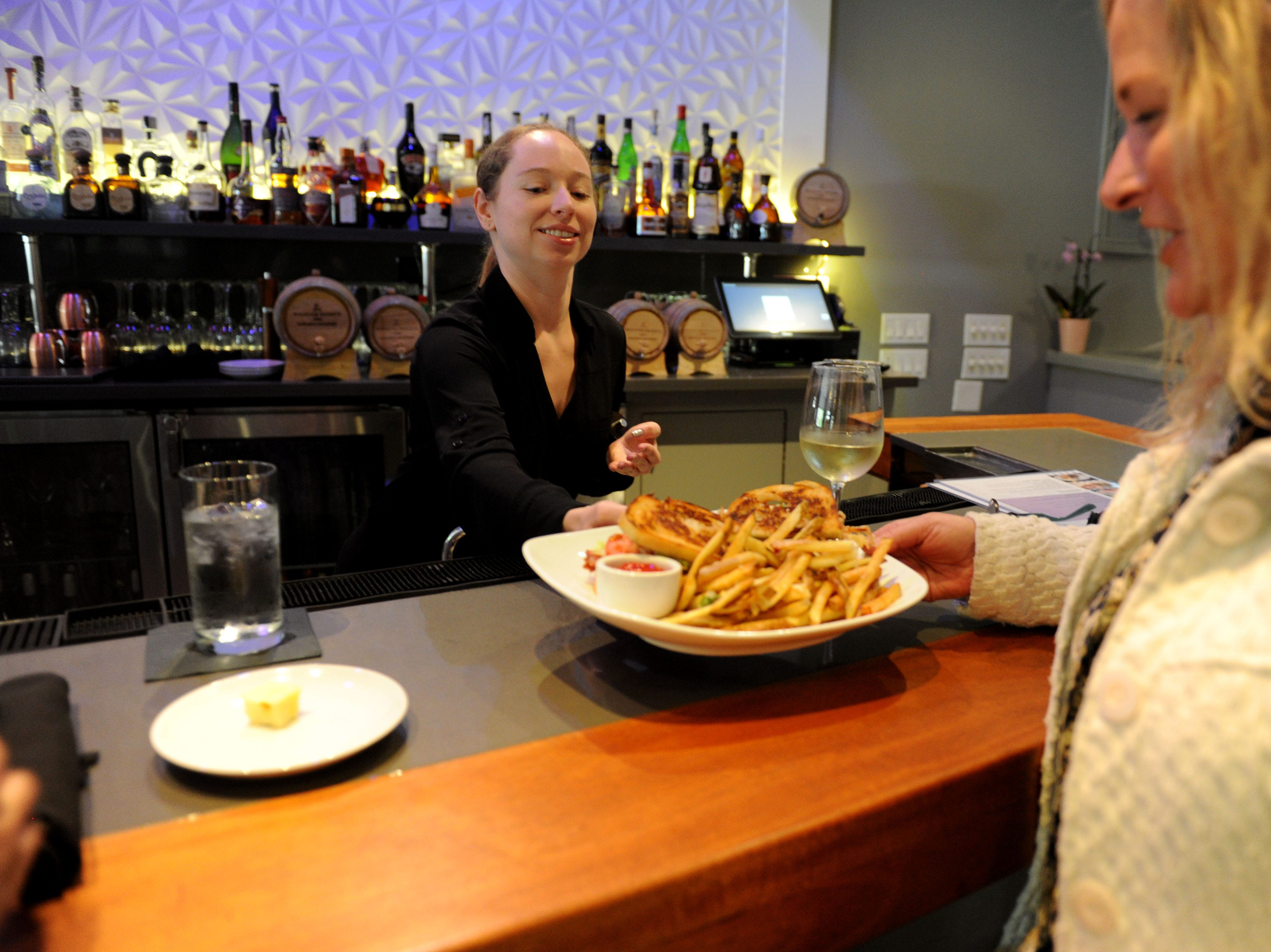 Erika Giroux, hostess at Slate Bistro & Craft Bar, in Camarillo serves Robin Reed the fresh soft shell crab sandwich with French fries.