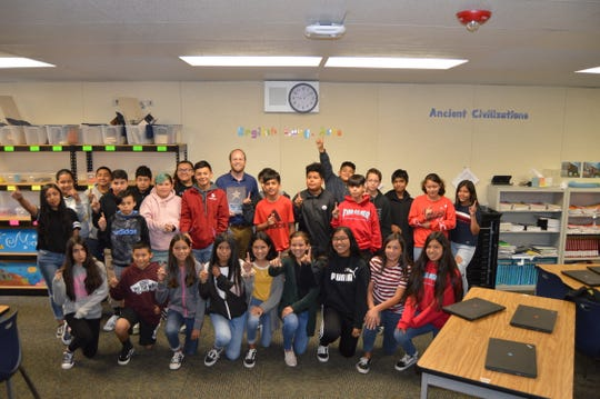 Isbell Middle School teacher Jan-Erik Sand stands with his students after being named Ventura County teacher of the year.
