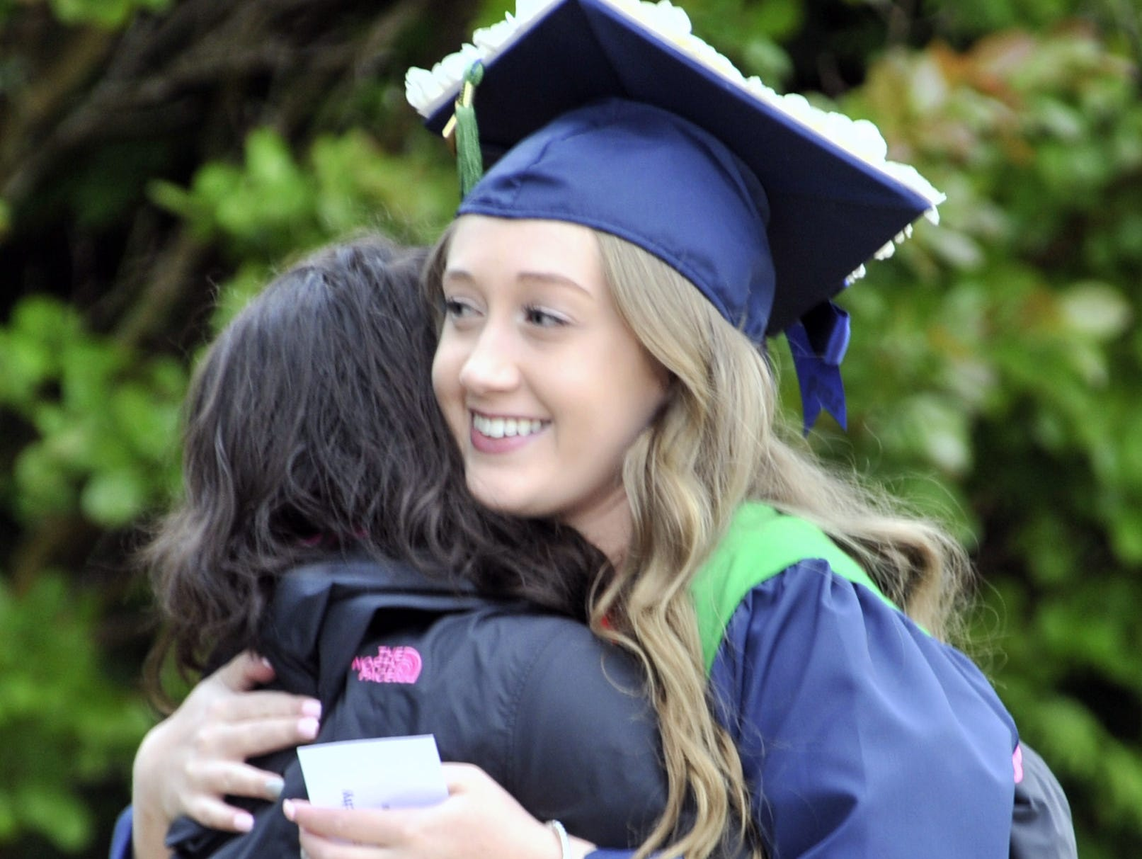 Taylor Beachy of Smyrna gets a hug from a friend before the commencement exercise at the Delaware Technical Community College's Terry Campus in Dover on Monday.