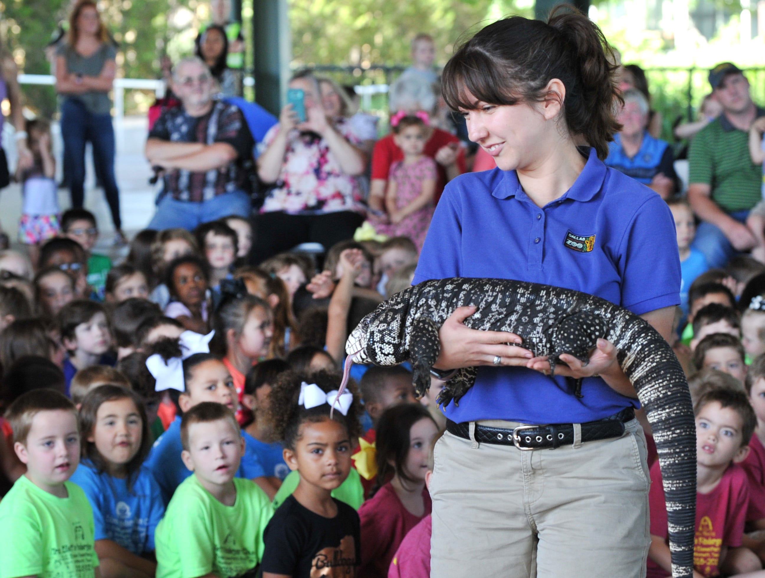 Dallas Zoo outreach specialist, Dianne Rivas shows Spock, a black and white Tegu, to a group of kids, Tuesday during the zoo's trip to the River Bend Nature Center.