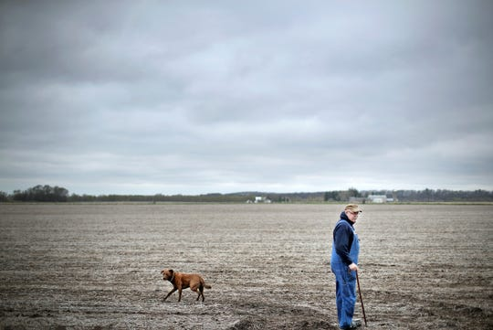 Roger Millard walks into the field behind his home with his dog Red, showing where the solar panels could be installed. There are no state regulations that address how far solar panels, such as those in a utility-scale solar development, need to be from residential property lines.