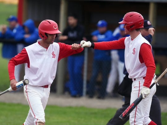 Reece Trowbridge is congratulated by a teammate after scoring the go-ahead run in the fifth inning of Sheridan's 2-1 win against visiting Washington Court House on Monday in a Division II sectional game near Thornville.