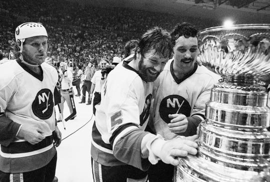 Fully bearded Islanders captain Denis Potvin looks at the Stanley Cup after winning the 1980 Final.