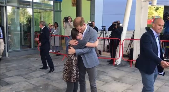 Prince Harry hugs Daisy Wingrove, who gave him a tour of Oxford Children's Hospital.