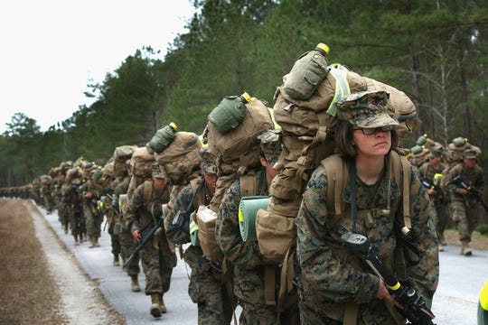 Marines participate in a 10 kilometer training march carrying 55 pound packs during Marine Combat Training (MCT) on February 22, 2013 at Camp Lejeune, North Carolina.