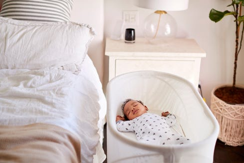 Three month old baby asleep in his cot beside a bed.