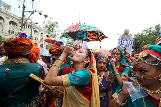 Bharatiya Janata Party (BJP) activists and dancers drink water as they walk a mass rally for BJP President Amit Shah in Kolkata. The results of parliamentary elections will be announced on May 23.