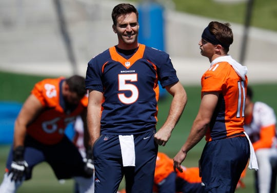 Denver Broncos quarterback Joe Flacco, left, jokes with wide receiver River Cracraft as they take part in drills during an NFL football organized training activity session at the team's headquarters.