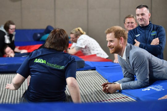 OXFORD, ENGLAND - MAY 13: Prince Harry checks out the trampolines where clients participate in Rebound Therapy session at OXSRAD.