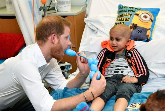 Prince Harry plays with a patient as he visits the Oxford Children's Hospital.