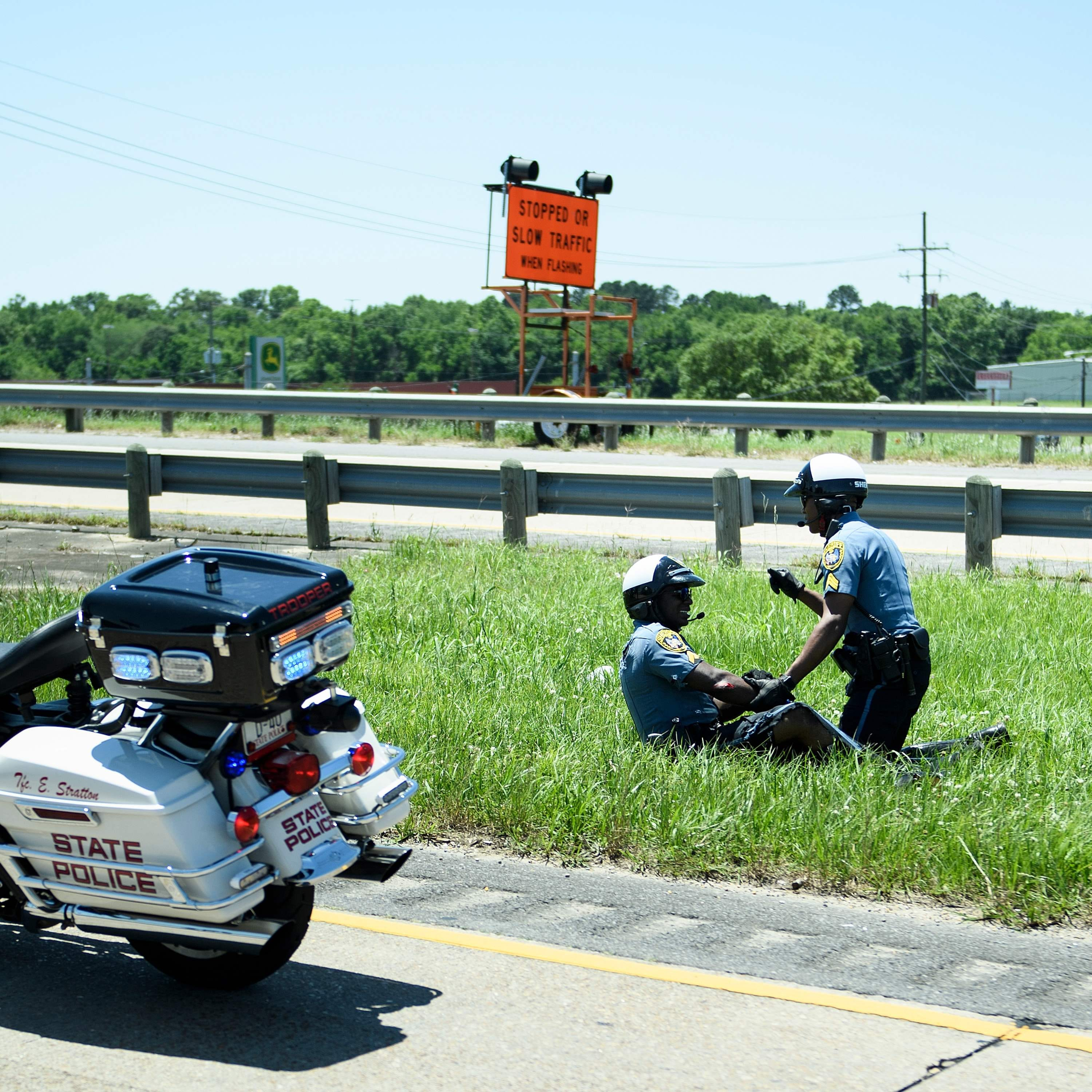 A police officer aids an officer involved in an accident while escorting a motorcade wit President Donald Trump from Chennault International Airport May 14, 2019, in Lake Charles, Louisiana. (