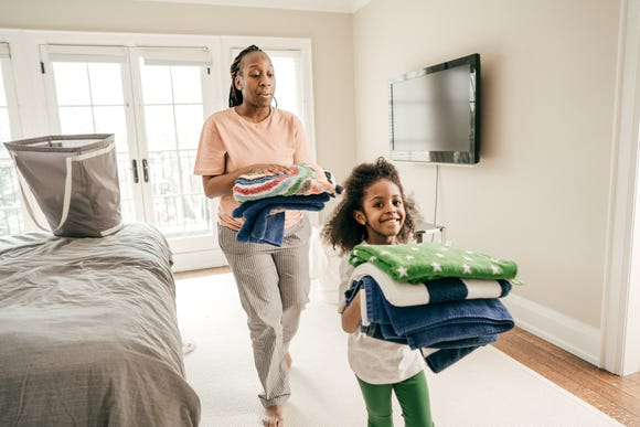 Daughter and mother folding clean towels.