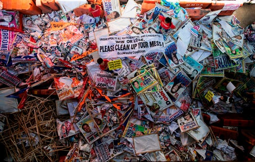 Environmental activists stand on campaign materials during a protest calling those who run for elective posts and the general public to conduct post-election cleanup activities in Manila.