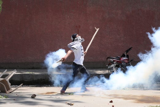 A student throws back a tear smoke shell at Indian police personnel during clashes in Srinagar, the summer capital of Indian Kashmir. Police fired tear smokes shells and pellets to disperse stone-throwing students. Protests erupted at several places on the third consecutive day in Indian Kashmir against alleged rape of a three-year-old girl.