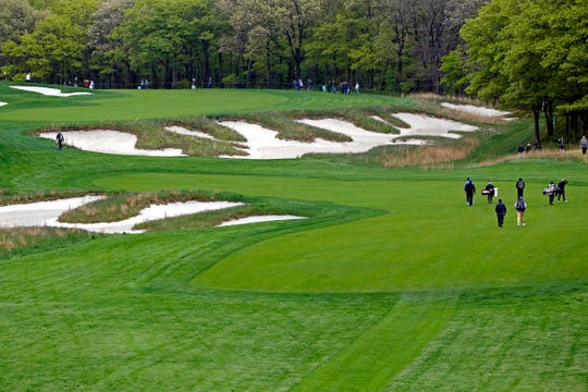 Golfers practice on the fifth hole of the Black Course at Bethpage State Park on Monday.