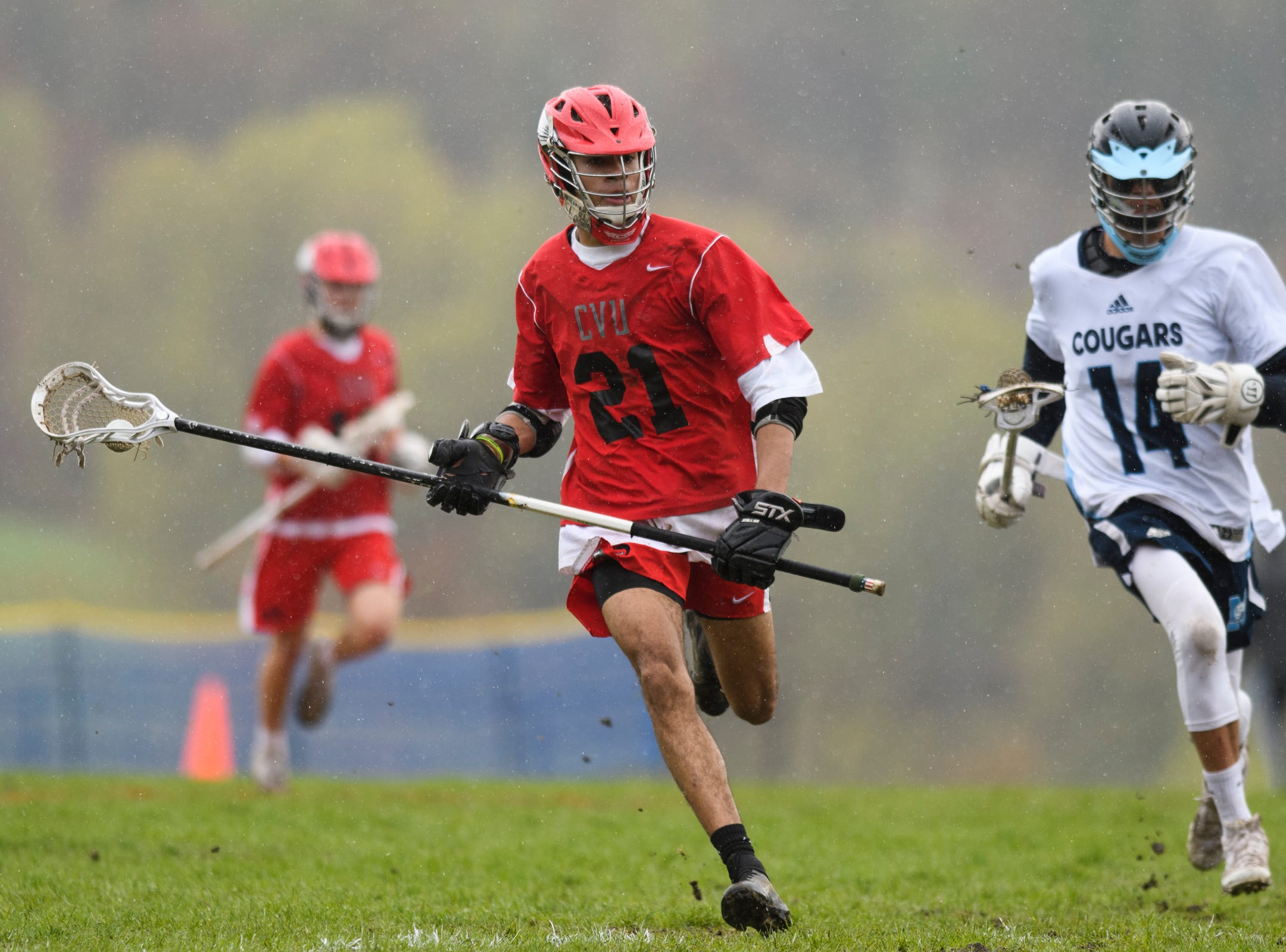 CVU's Noah Martin (21) runs down the field with the ball during the boys lacrosse game between the Champlain Valley Union Redhawks and the Mount Mansfield Cougars at MMU High School on Tuesday afternoon May 14, 2019 in Jericho, Vermont.
