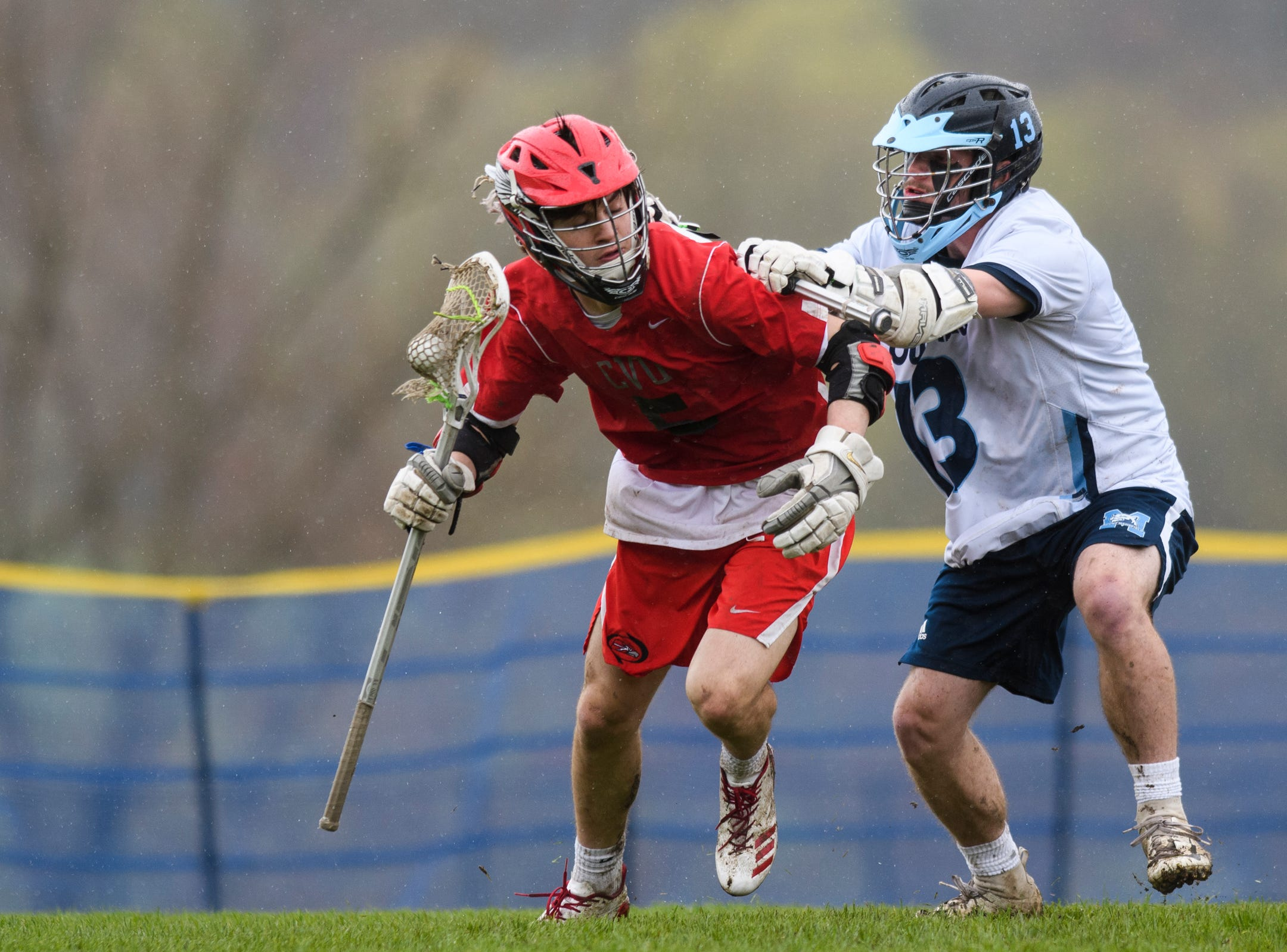 MMU's Dylan Davis (13) checks CVU's Jake Schaefer (5) during the boys lacrosse game between the Champlain Valley Union Redhawks and the Mount Mansfield Cougars at MMU High School on Tuesday afternoon May 14, 2019 in Jericho, Vermont.