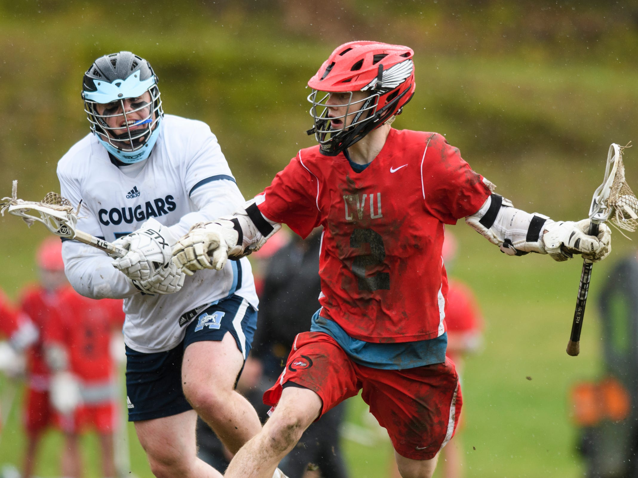 CVU's Sean Gilliam (2) runs past MMU's Will Half (10) during the boys lacrosse game between the Champlain Valley Union Redhawks and the Mount Mansfield Cougars at MMU High School on Tuesday afternoon May 14, 2019 in Jericho, Vermont.