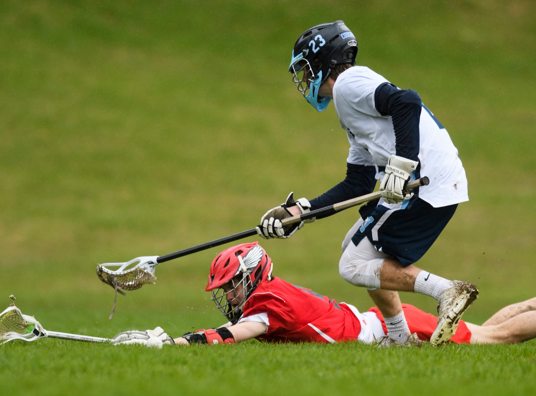 CVU's Jake Schaefer (5) falls down as he battles for the ball with MMU's Matt Reinfurt (23) during the boys lacrosse game between the Champlain Valley Union Redhawks and the Mount Mansfield Cougars at MMU High School on Tuesday afternoon May 14, 2019 in Jericho, Vermont.