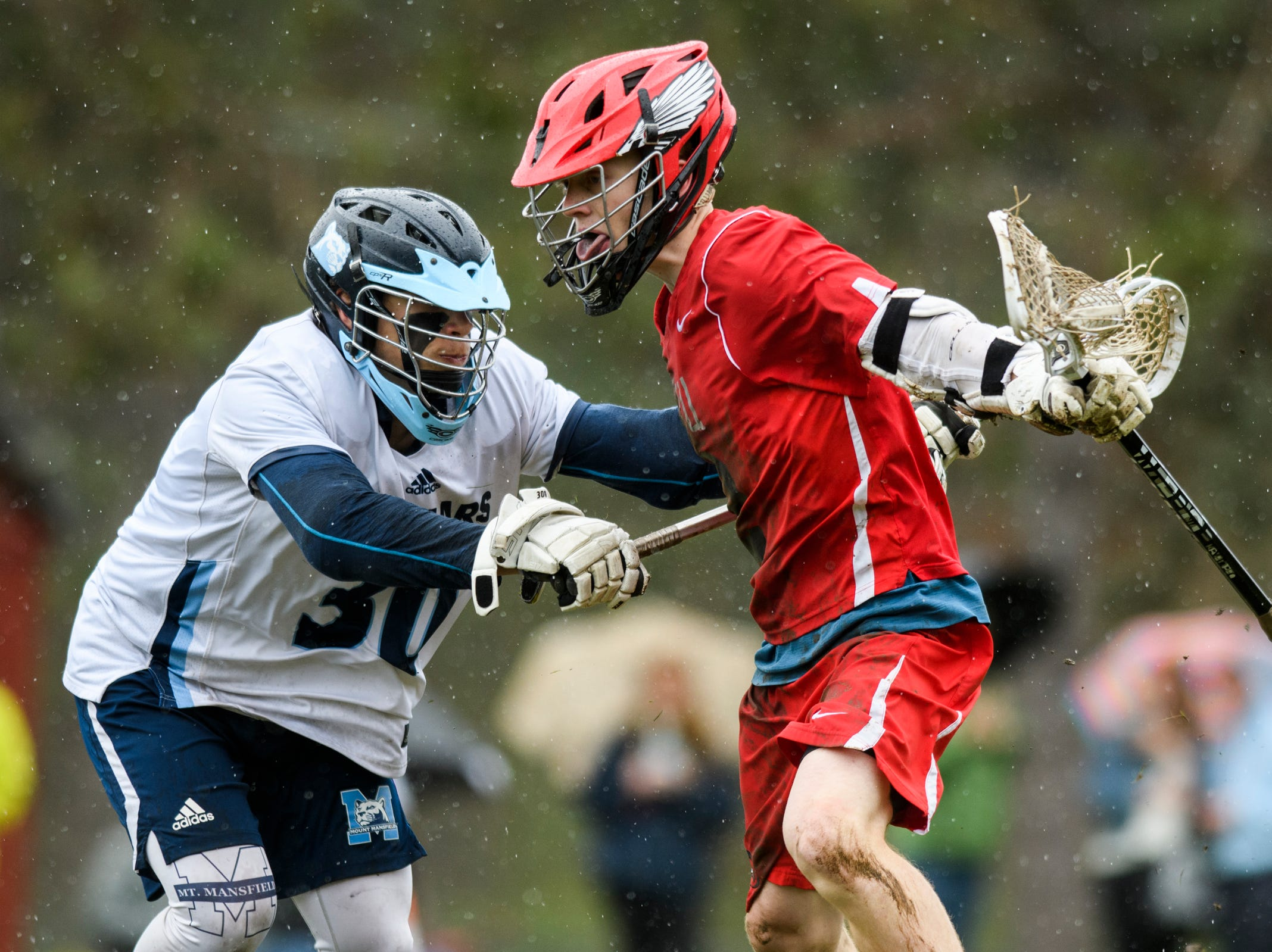 MMU's David Seymour (30) checks CVU's Sean Gilliam (2) during the boys lacrosse game between the Champlain Valley Union Redhawks and the Mount Mansfield Cougars at MMU High School on Tuesday afternoon May 14, 2019 in Jericho, Vermont.