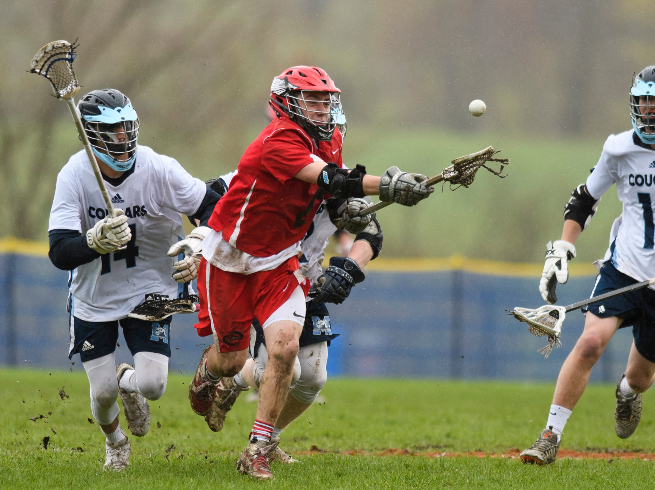 CVU's Nikos Carroll (6) scoops up the ball during the boys lacrosse game between the Champlain Valley Union Redhawks and the Mount Mansfield Cougars at MMU High School on Tuesday afternoon May 14, 2019 in Jericho, Vermont.