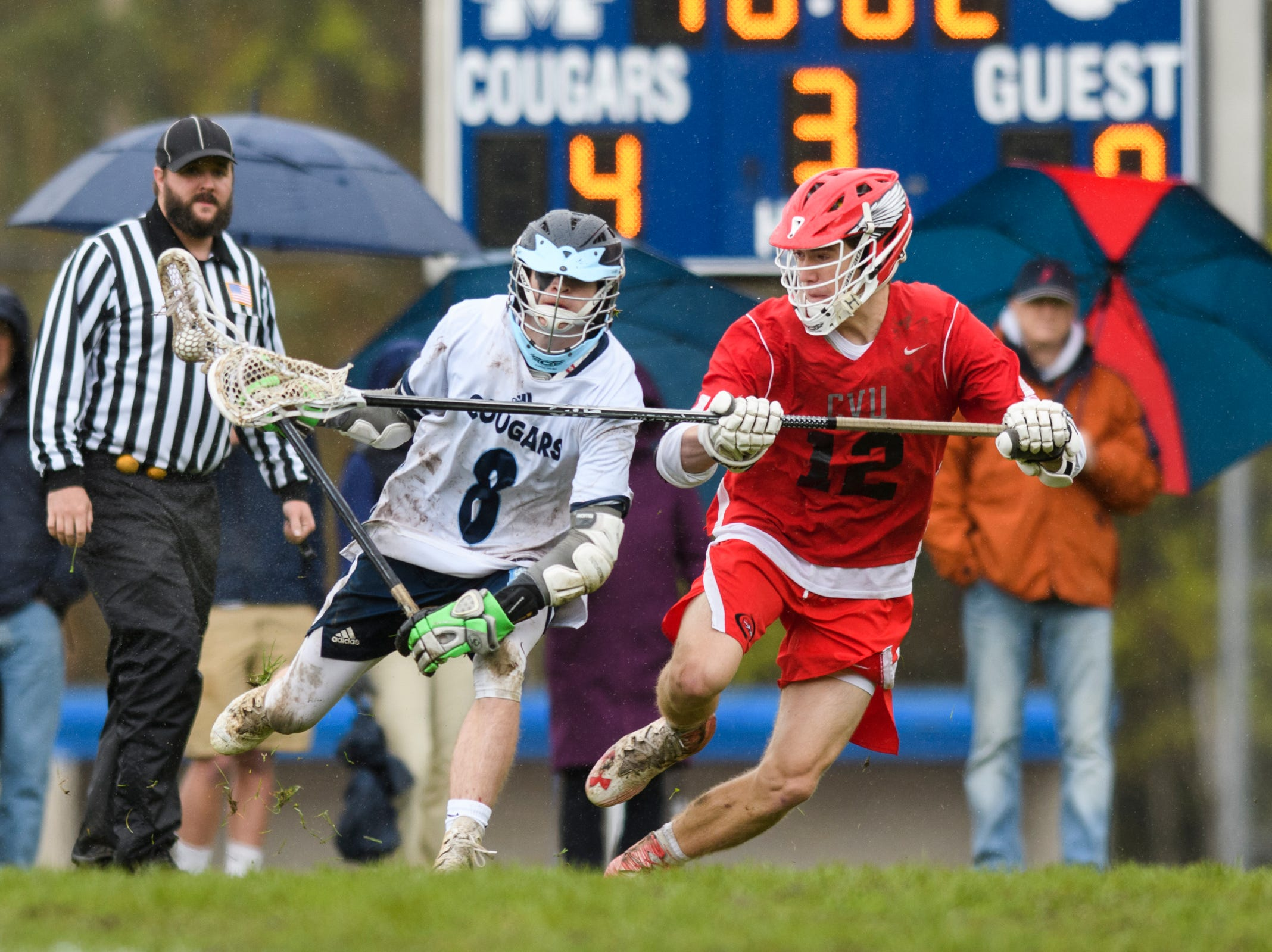 MMU's Teddy Waite (8) tries to run past CVU's Aidan Trus (12) with the ball during the boys lacrosse game between the Champlain Valley Union Redhawks and the Mount Mansfield Cougars at MMU High School on Tuesday afternoon May 14, 2019 in Jericho, Vermont.