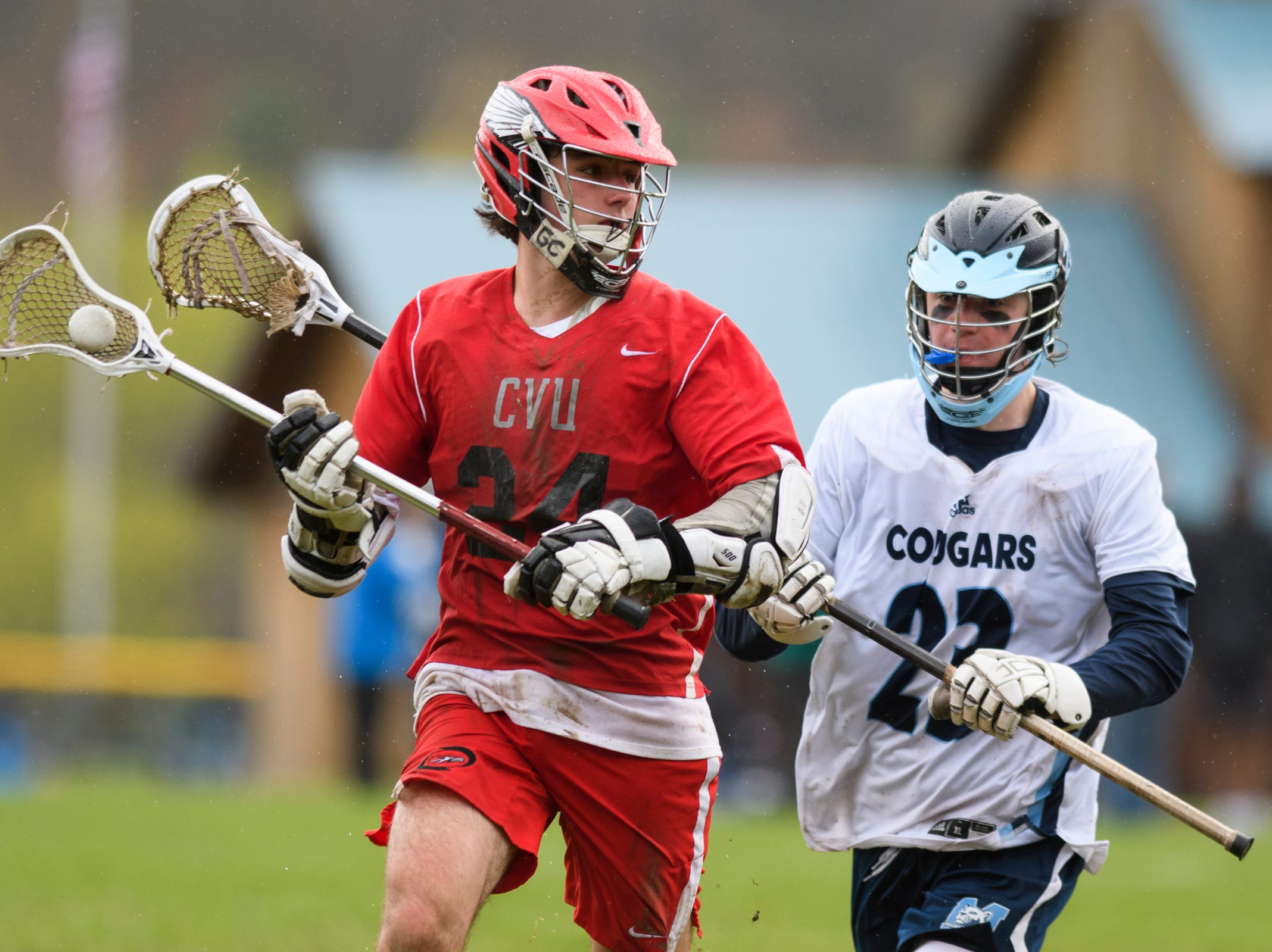 CVU's Nate Cuttitta (24) runs past MMU's Matt Reinfurt (23) during the boys lacrosse game between the Champlain Valley Union Redhawks and the Mount Mansfield Cougars at MMU High School on Tuesday afternoon May 14, 2019 in Jericho, Vermont.