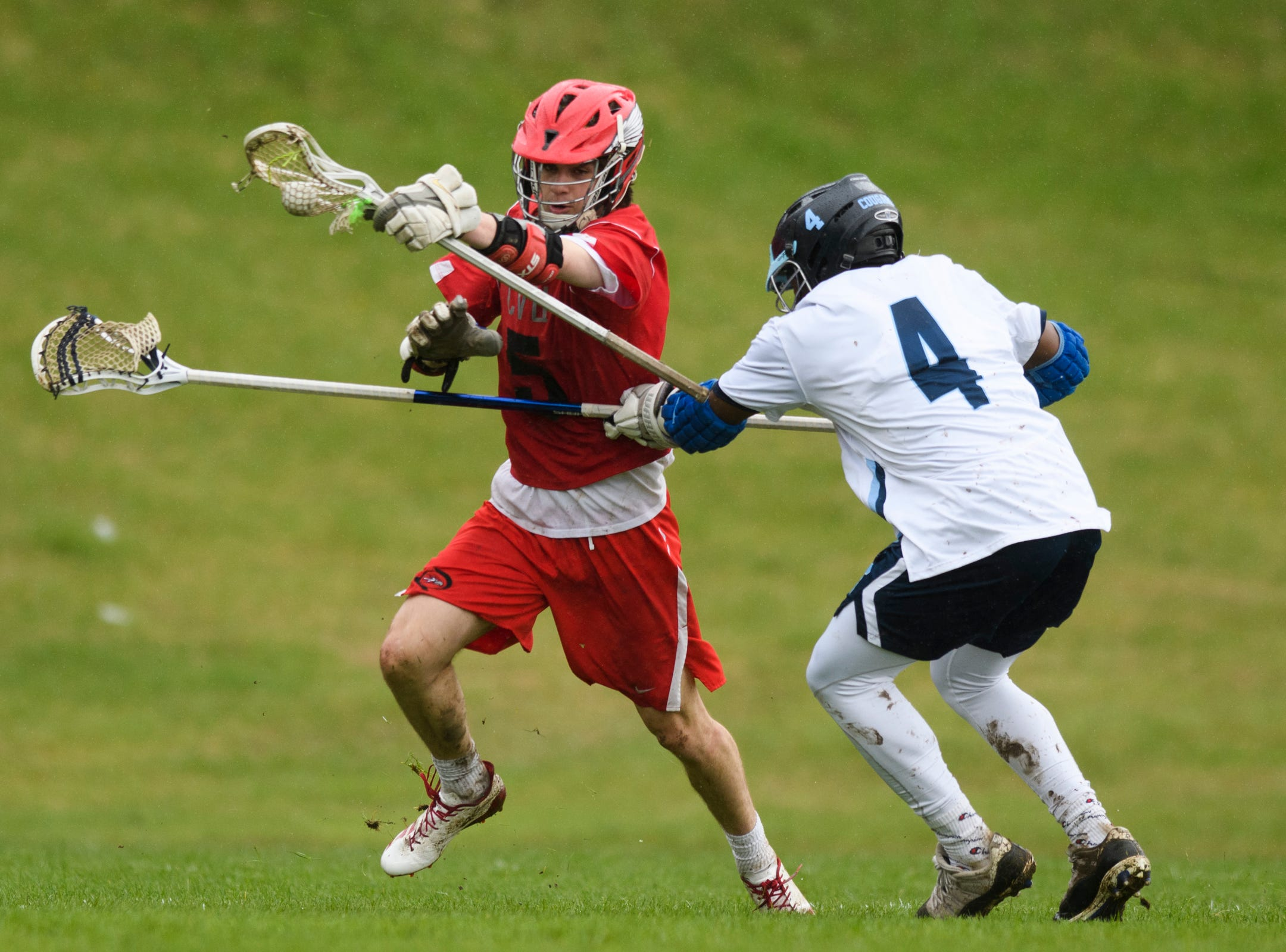 CVU's Jake Schaefer (5) tries to run past MMU's Jehric Hackney (4) with the ball during the boys lacrosse game between the Champlain Valley Union Redhawks and the Mount Mansfield Cougars at MMU High School on Tuesday afternoon May 14, 2019 in Jericho, Vermont.