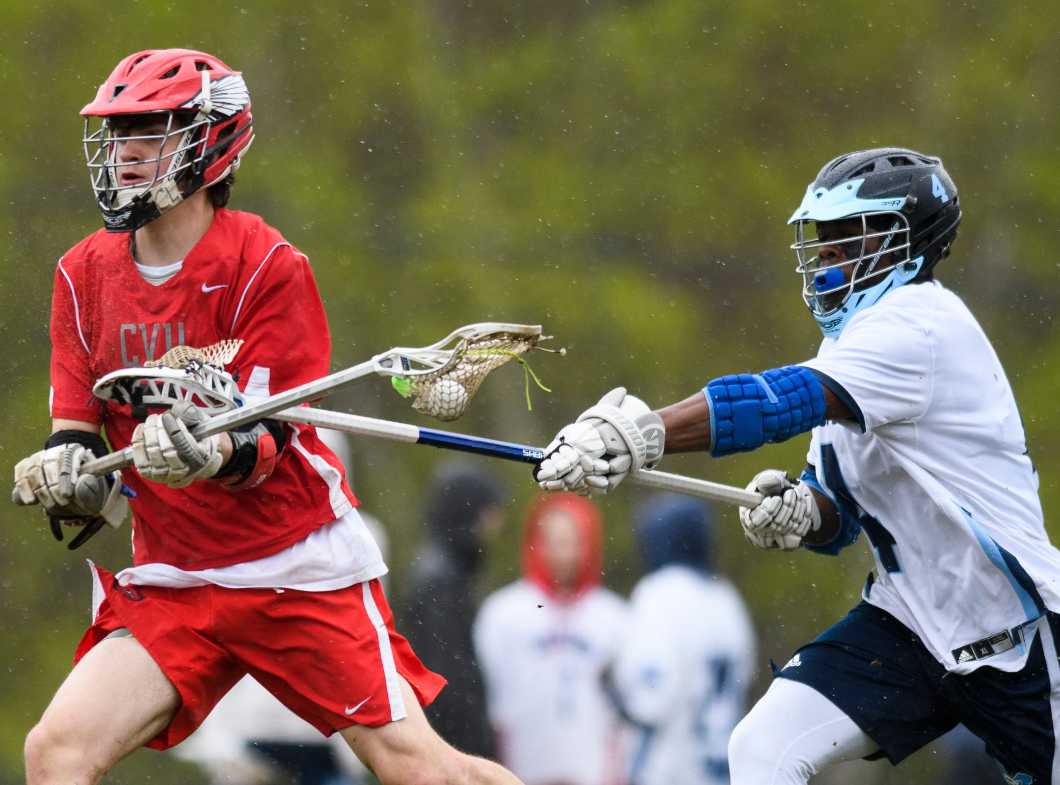 MMU's Jehric Hackney (4) stick checks CVU's Jake Schaefer (5) during the boys lacrosse game between the Champlain Valley Union Redhawks and the Mount Mansfield Cougars at MMU High School on Tuesday afternoon May 14, 2019 in Jericho, Vermont.