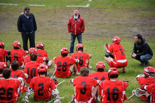 CVU head coach Dave Trevthick talks to the team during halftime in the boys lacrosse game between the Champlain Valley Union Redhawks and the Mount Mansfield Cougars at MMU High School on Tuesday afternoon May 14, 2019 in Jericho, Vermont.