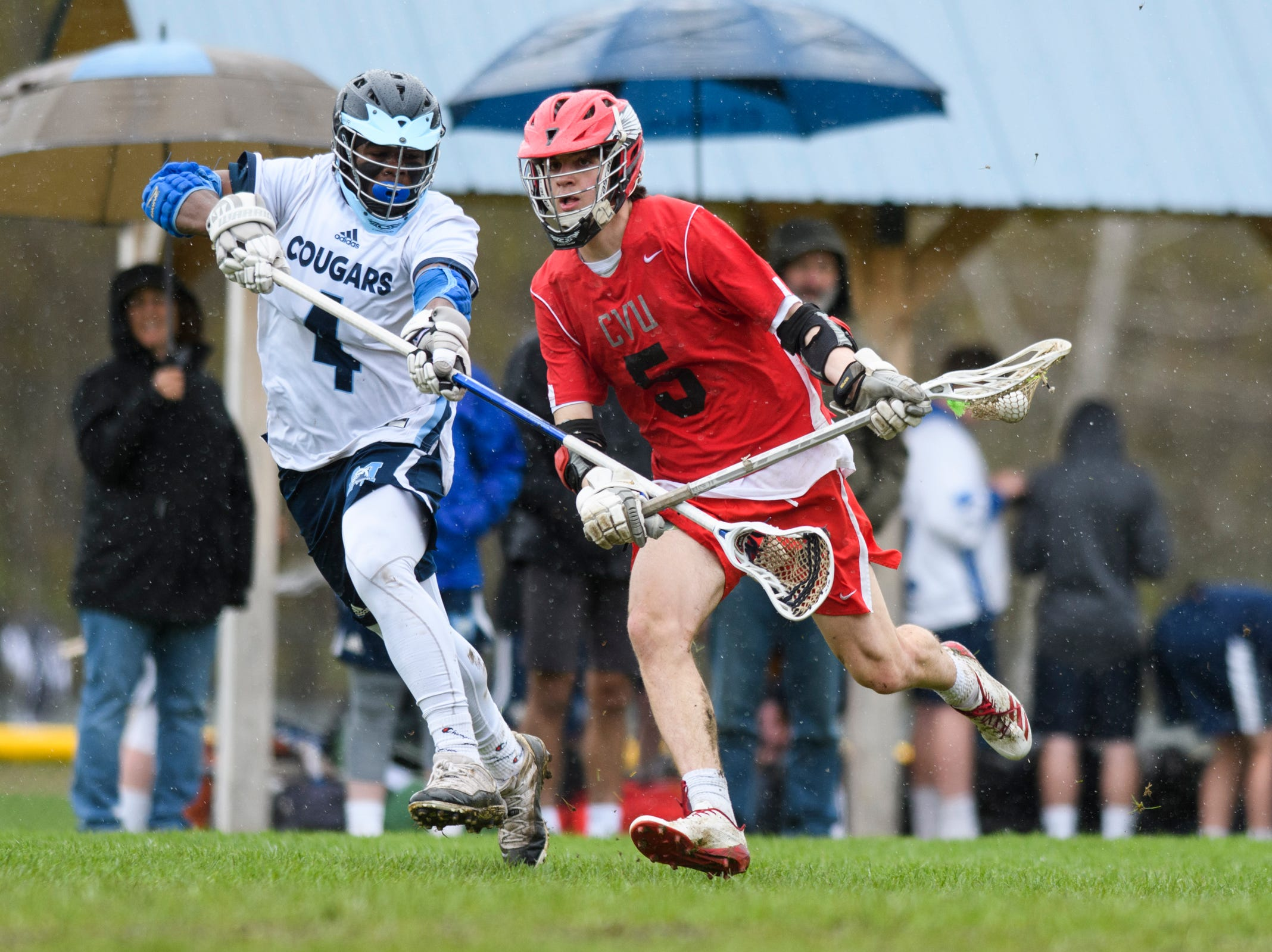CVU's Jake Schaefer (5) runs past MMU's Jehric Hackney (4) with the ball during the boys lacrosse game between the Champlain Valley Union Redhawks and the Mount Mansfield Cougars at MMU High School on Tuesday afternoon May 14, 2019 in Jericho, Vermont.