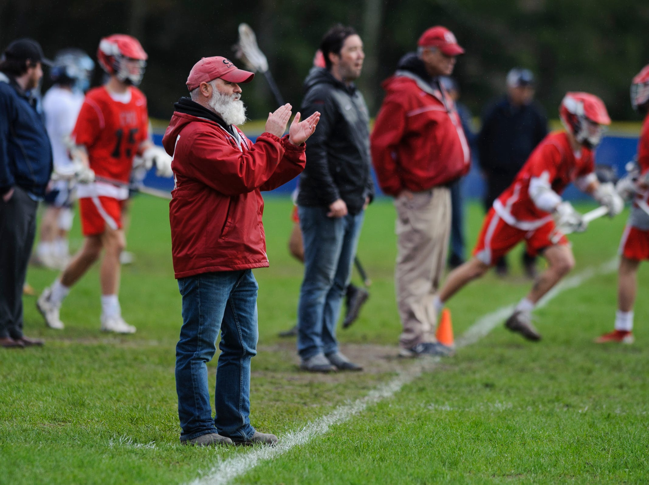 CVU head coach Dave Trevithick cheers for the team on the field during the boys lacrosse game between the Champlain Valley Union Redhawks and the Mount Mansfield Cougars at MMU High School on Tuesday afternoon May 14, 2019 in Jericho, Vermont.